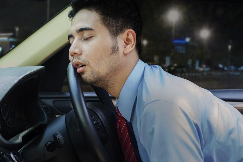 Erschöpfter Mann am Lenkrad eingeschlafen